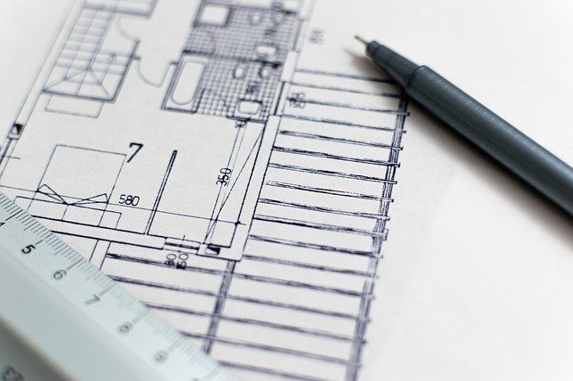 A metallic ruler and black pen laying on top of a sample construction blueprint. Finish carpenters looking to get the C-6 License must know how to read blueprints