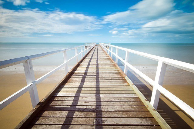 a long pier facing out into the ocean