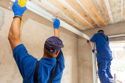 two contractor installing a garage door. article details what you need to do after you pass the CSLB law and business exam