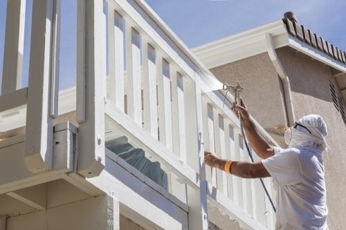 A painting contractor spraying a wooden porch. The California painting contractor license test will cover law and trade