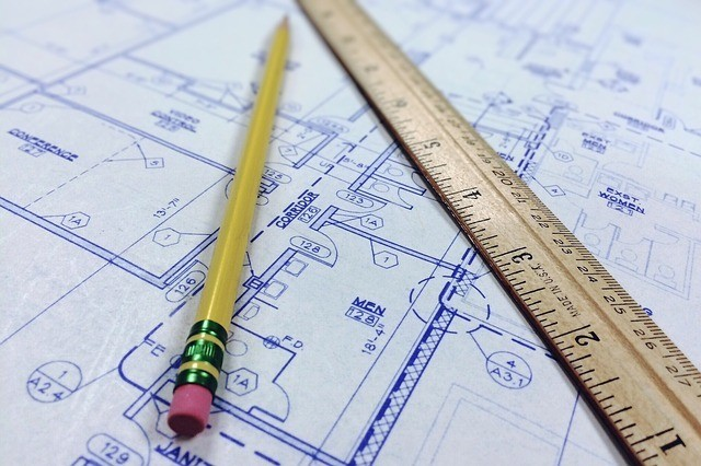 a yellow pencil and wooden ruler laying on top of a white piece of paper that appears to be a construction blueprint