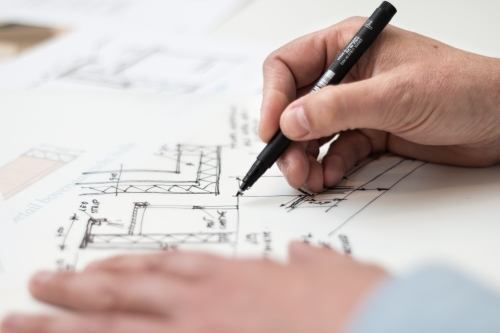 a person holding a pen writing a construction blueprint