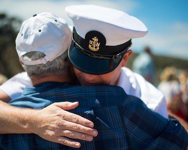 a naval veteran hugging an old man. getting a contractor license in california if you are a military veteran shouldnt be a complicated process