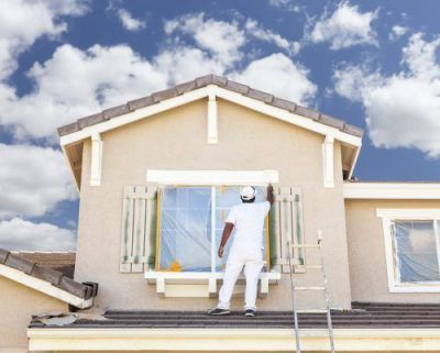 image of a painting contractor on top of a house painting a window seal. To get a painting license in california you must meet the CSLB's basic requirements