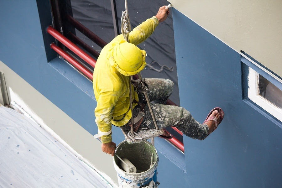 A painter hanging from a chord painting a building wall. To get the C-33 painting license in california you have to meet basic requirements