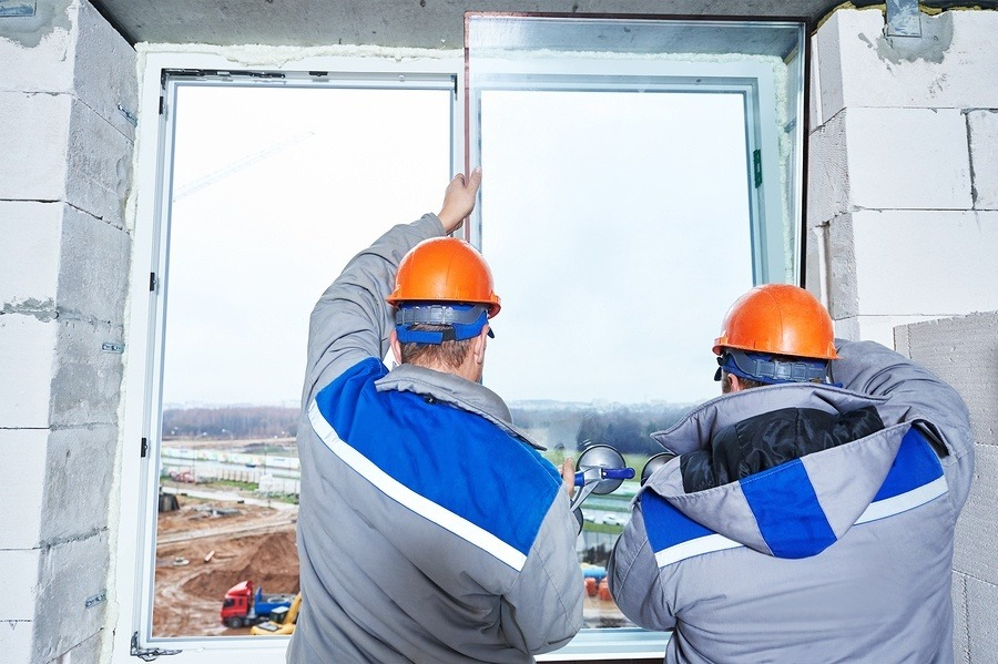 two glazing contractors installing a window in a building