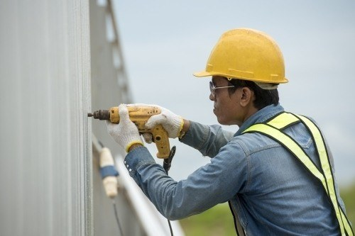 a fencing contractor using an electric powered drill on a large fence