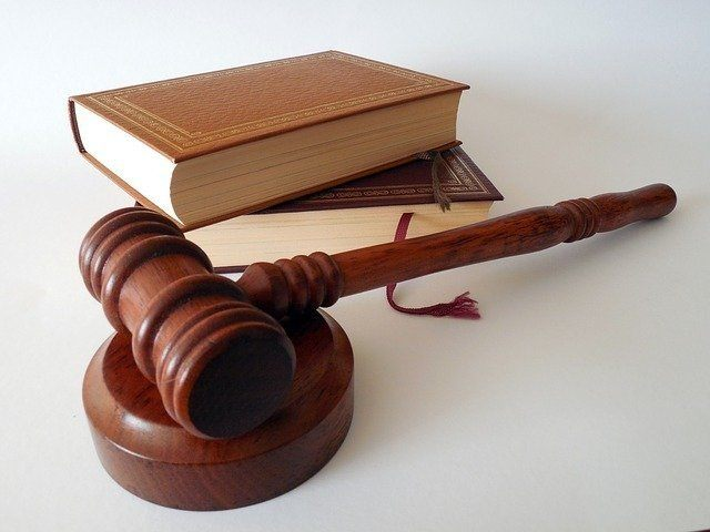 two law books and a wooden gavel. when applying for the C39 roofing license you will need to do fingerprinting so it is important that you are 100% honest about your criminal history
