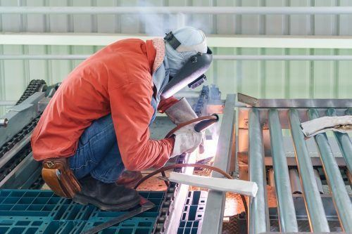 A welding contractor in the process of welding a large piece of steel. The CSLB may request to see documentation of your welding experience when applying for the C-60 license