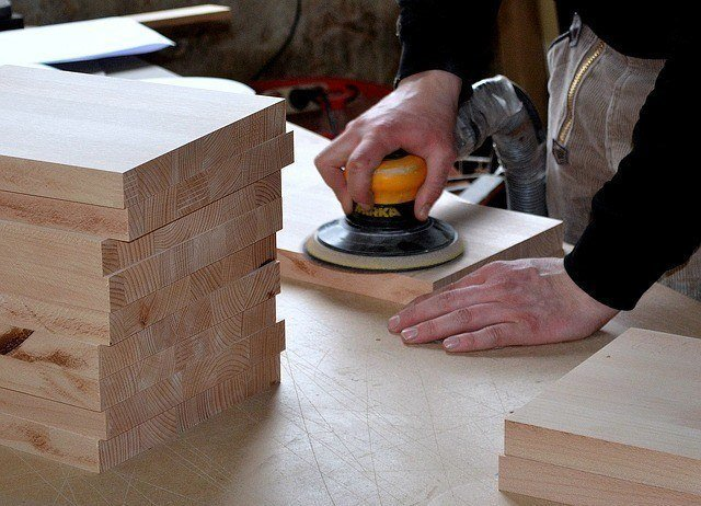 a wood worker sanding a block of wood using a machine