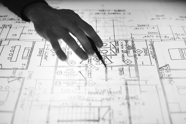 a hand holding a pencil pointing to something on a construction blueprint. california does not have a state license for mold remediation