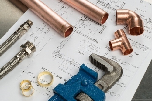 a wrench and some plumbing accesories laying on top of a construction blueprint. to pass the plumbing test you should be sure to follow the following 5 tips
