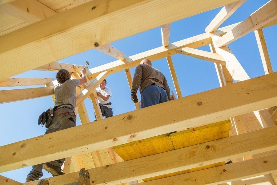 several carpenters building a house