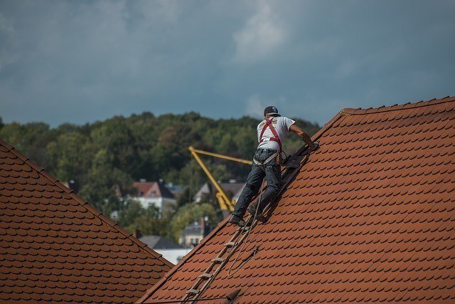a roofer performing repairs on top of a residential home.