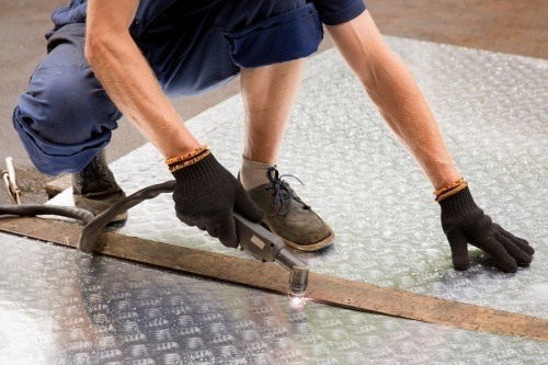 a contractor using scissors to cut a large slab of sheet metal. contractors looking to get the sheet metal license should follow these 5 steps