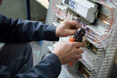 Electrician assembling industrial control cubicle in workshop. Close-up photo. to get the nevada electrical license you will need to pass a two part exam