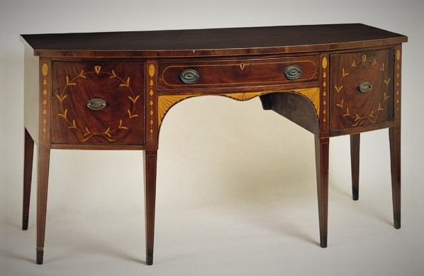 Mahogany bow-front sideboard with bell-flower, fan, leaf and line inlay; long drawer flanked by deep drawer and door.