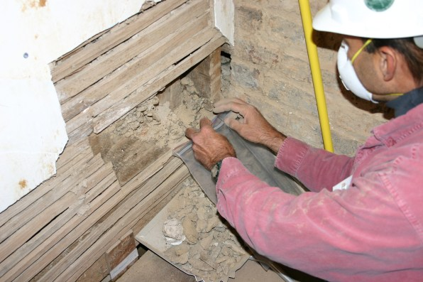 Steve Chronister removes plaster from the lower portion of the truss wall in Room 206.