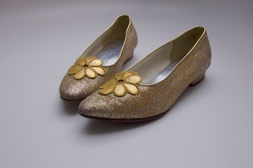 A pair of Marion duPont Scott's shoes featuring gold glitter and floral accent.