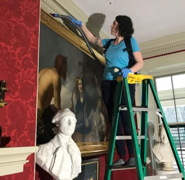 "Curatorial & Collections Assistant, Leanna, removed dust from the gilt frame of ""Pan, Youths & Nymphs."""