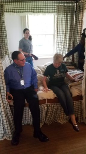 Staff members test out the reproduction four-post bed in the Interactive Room at Montpelier, April 2019.