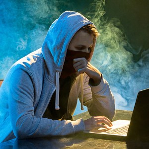 Hooded hacker using a laptop in a smoky room