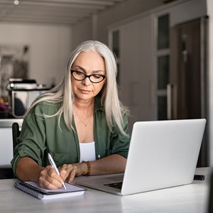 Woman using laptop to write along with paper and pen