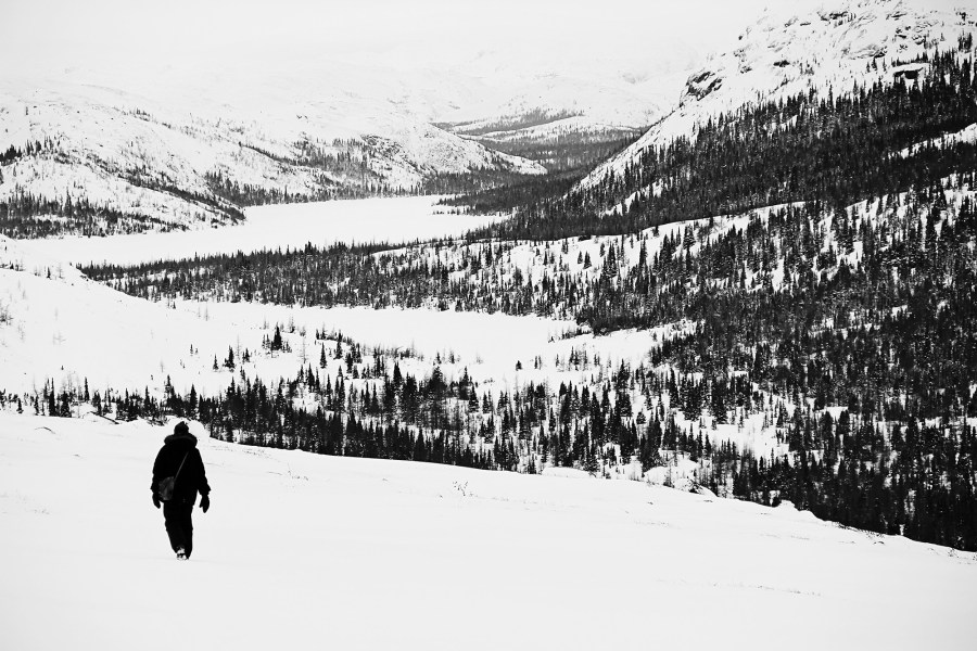 Image of person in black winter clothing walking in snowy mountain landscape.