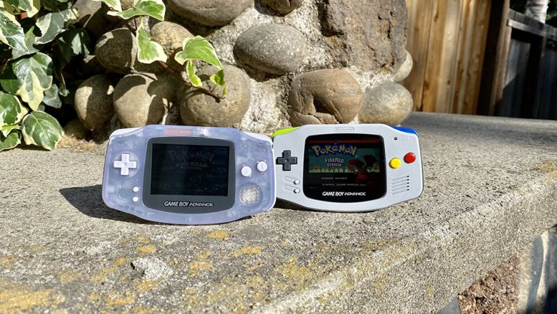 Two original Game Boy Advances outside in the sun with barely visible screens