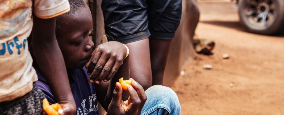 Un enfant africain et ses soeurs mangeant des fruits.