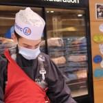 Un employé d'un centre Leclerc découpant de la viande.