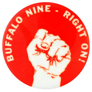 A red button with a clenched fist in the middle, with BUFFALO NINE - RIGHT ON! written around the edge