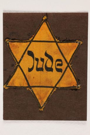 """W yellow Star of David with the word """"JUDE"""" in the middle"""