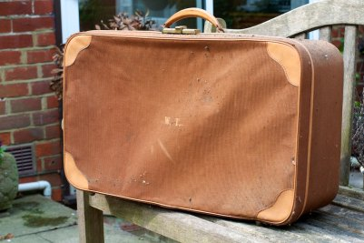 A photograph of a dirty, old, brown suitcase