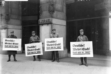 a black and white photograph of three protesters in front of a large concrete building holding