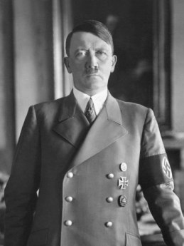Adolph Hitler. Portrait of a white man with dark hair, military style clothing, and a tiny black mustache