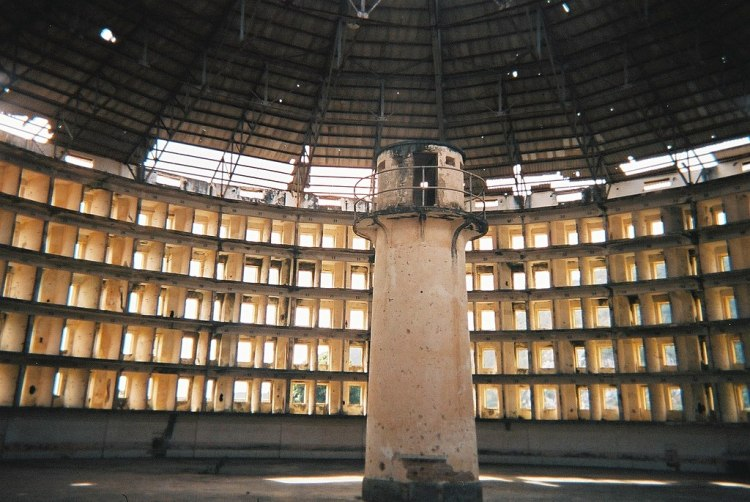 An image of an abandoned prison with a central guard tower surrounded by a round wall with individual cells built into it