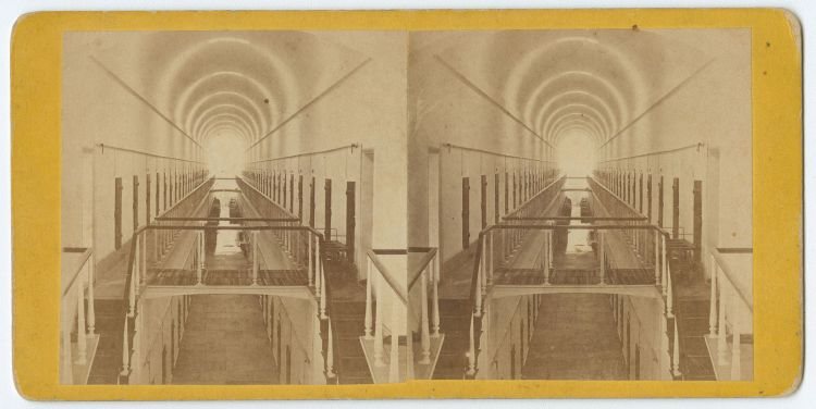 a vintage photograph of a long hallway with wooden doors lining the wall