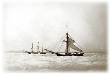 A sepia toned photograph of two sailing ships frozen in polar ice