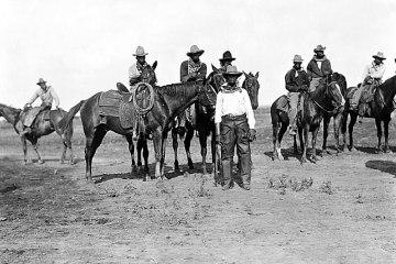 a black and white photograph of black cowboys on horseback