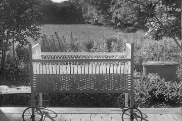 a black and white photograph of a cradle with wheels on a porch