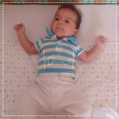 Posicione o bebê sobre um tecido quadrado. Pode ser uma manta, uma fralda, flanela, malha, até lençol. O importante é que os ombros do bebê estejam na linha do quadrado