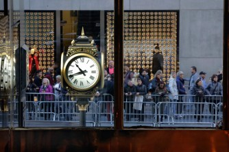 People stop to look at the front of Trump Tower on Fifth Avenue, in New York, Friday, Nov. 11, 2016. Trump's presidential victory has increasingly turned the streets around his Trump Tower penthouse home into a hardened, national security location. The trendy boutiques, shops and restaurants in and around Trump's Fifth Avenue home say they are already seeing business drop and aggravation rise.(AP Photo/Richard Drew)