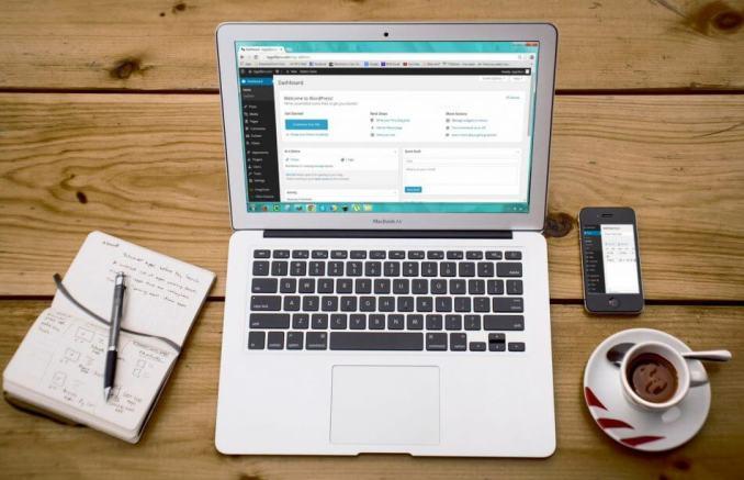 foto laptop sedang buka website blog wordpress dengan secangkir kopi dan buku disampingnya