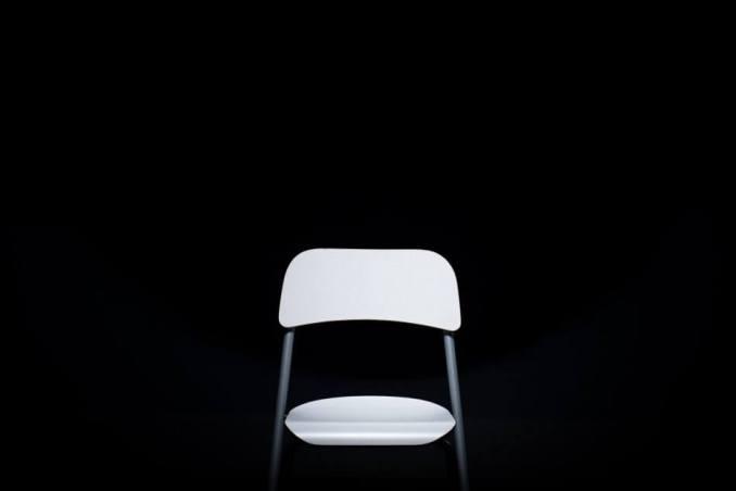 foto kursi metal sekaligus plastik putih dengan latar hitam