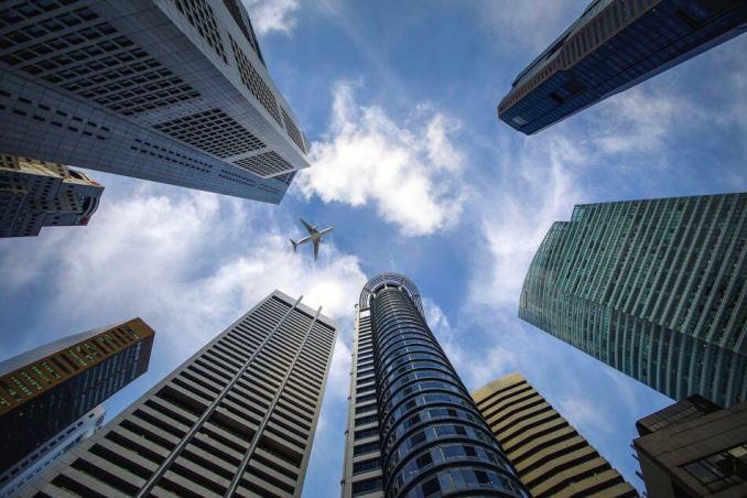 foto gambar beberapa gedung bertingkat dari arah bawah, foto perusahaan dengan pesawat melewati atas gedung
