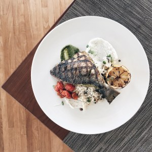 Grilled whole sea bream on rice with roasted cherry tomatoes