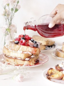 Drizzling more raspberry syrup on top of french toast