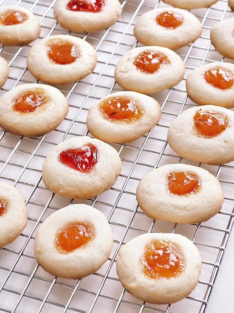 Cute heart-shaped thumbprint cookie on a cooling rack