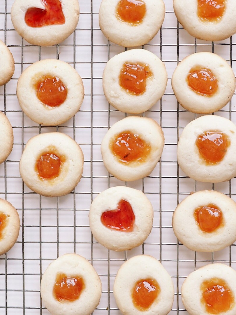 Thumbprint cookies cooling on a cooling rack